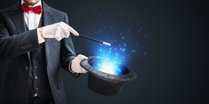 Magician or illusionist is showing magic trick with wand and hat on dark background.