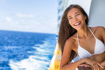 Wall Mural - Cruise ship Caribbean travel vacation Asian woman tourist in bikini enjoying deck on troipcal holiday. Smiling happy girl having fun on boat. Portrait lifestyle.