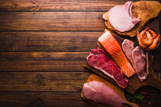 Group of animal proteins, chicken, meat, fish and pork on a wood background