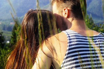happy stylish hipster couple hugging on background mountains in summer through unusual grass view