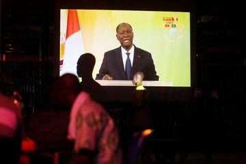 People watch speech of Ivory Coast President Ouattara on a screen in Palmeraie, Abidjan