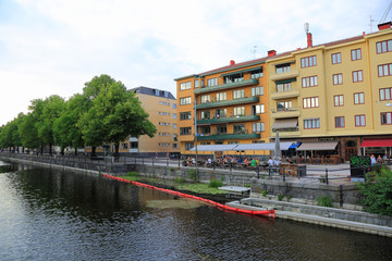 Beautiful landscape view of riverside, Uppsala, Sweden, Europe. Yellow buildings and green trees on blue sky background.