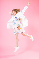 A teenage girl in light clothes jumped on a pink background.