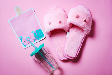 Cute pink flat lay with fluffy home slippers, face mask and plastic bottle isolated on pink background. Girls stuff. Relaxation concept. Top view