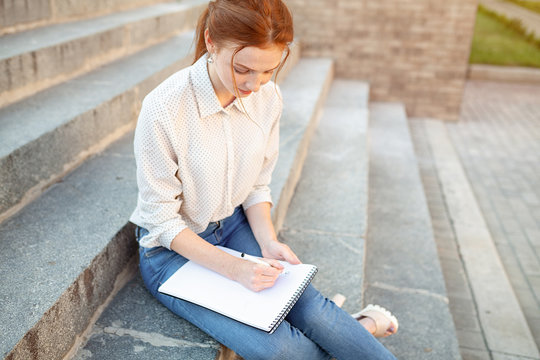 A beautiful young redhaired girl writes a romantic love letter sitting on a stairs near the institute. Student love. Or homework