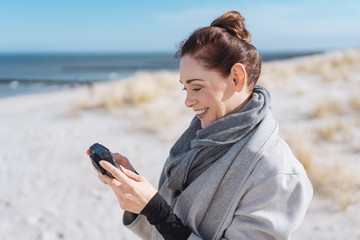 Delighted youn woman reading an sms on a mobile