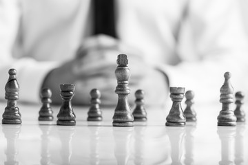 Monochrome image of businessman sitting in front of dark chess pieces
