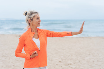 Angry woman on a beach making a halt gesture