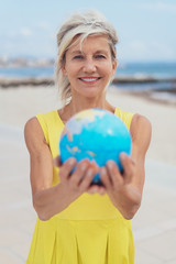 Attractive woman holding out a world globe