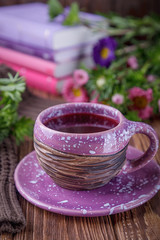 Autumn composition. Fruit tea, books and flowers asters on a wooden background