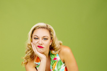 Portrait of a bored and unhappy blonde woman, isolated on green studio background