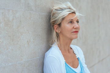 Worried woman standing thinking leaning on a wall