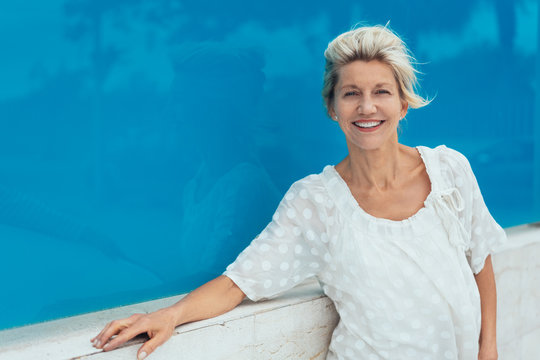 Mature smiling woman against blue background