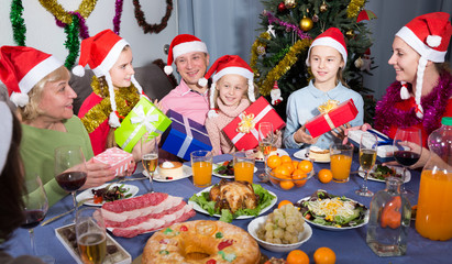 Portrait of happy family who is sitting with gifts in time celebrating New Year