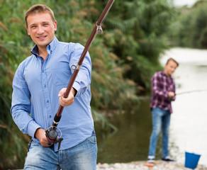 Man fishing using rod on lake