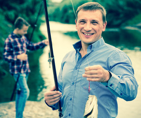 man showing fresh catch fish.