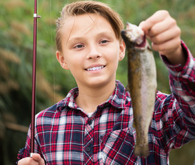 Positive teenage boy holding catch fish in hands