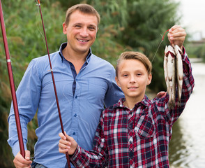 Adult father with son looking at fish on hook