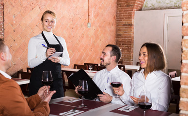 woman waiter receiving order from guests in restaurant