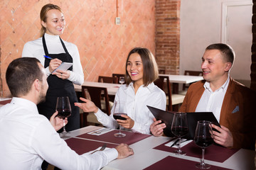 Cheerful female waiter writing down order