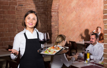 woman waiter demonstrating restaurant to visitors