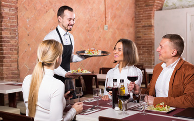 happy waiter placing order in front of guests