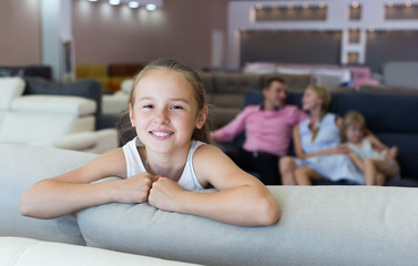 Postrait of cute child girl is standing near new sofa