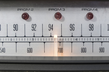 Macro close up of vintage radio tuner dial with lit needle.