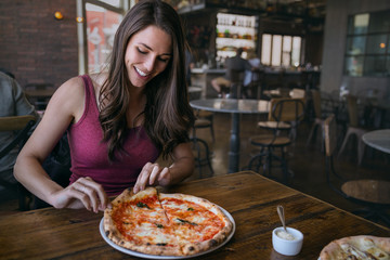 Smiling woman at hip artisanal pizzeria grabbing a slice of delicious craft pizza