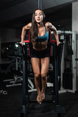 Fitness woman doing push-ups on uneven bars in crossfit gym.