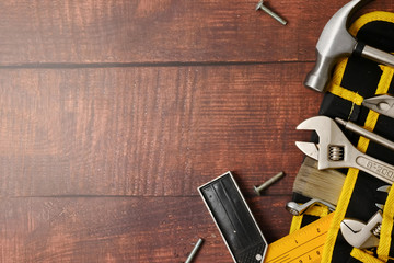 Construction worker belt with tools on wooden table background. Free space for text