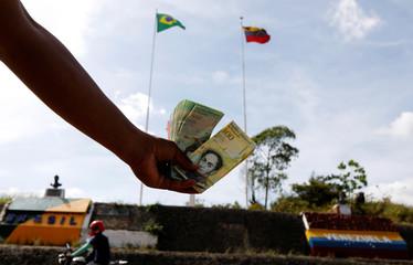 A Venezuelan man displays Venezuelan money at the border with Venezuela, seen from the Brazilian city of Pacaraima