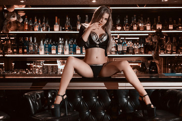 Dance in a bar concept. Pole dance concept. Girl with a beautiful figure and long legs dancing on the bar. Ideal figure. Creative magenta toning Wall mural