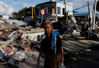 A man walks near the ruins of a shop after an earthquake hit on Sunday in Pemenang