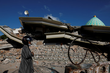 A woman walks near the collapsed ruins of a mosque after an earthquake hit on Sunday in Pemenang, Lombok island