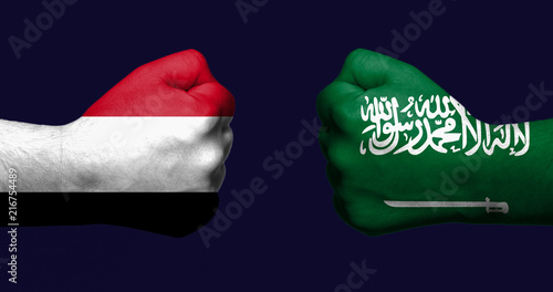 Flags of Yemen and Saudi Arabia painted on two clenched fists facing