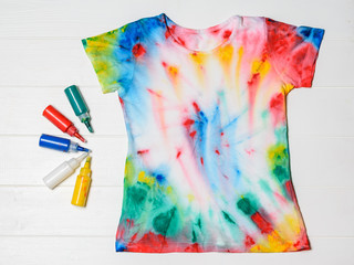 e716b429 T-shirt painted in tie dye style on a blue background. Flat lay ...