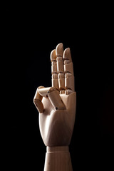 wood Mannequin, hand three on the black background.