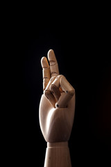 wood Mannequin, hand on the black background.
