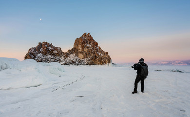 Travelling in winter, photographer carrying camera tripod at frozen lake Baikal in Siberia, Russia