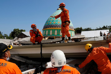 Rescuers and policemen talk on top of a collapsed mosque as they try to find survivors after an earthquake hit on Sunday in Pemenang, Lombok Island