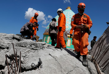 Rescuers and policemen walk on top of a collapsed mosque as they try to find survivors after an earthquake hit on Sunday in Pemenang, Lombok Island
