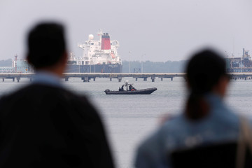 Marine police patrol the waters as members of the media wait for the arrival of seized luxury yacht Equanimity, belonging to fugitive Malaysian financier Low Taek Jho, at Boustead Cruise Terminal in Port Klang