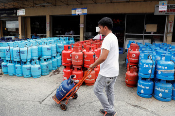 A man pushes a cart with an empty LPG canister in front of an LPG shop in Paranaque, Metro Manila