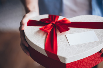 Close up of man hands giving a decorative present giftbox with empty white card - with copy space to insert text.