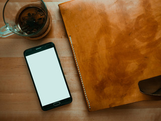Flat lay of leather bag smartphone and tea cup.