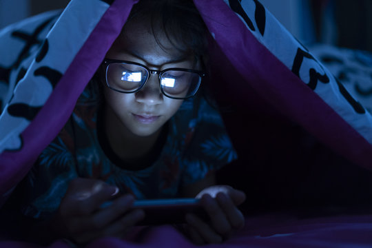 Girl wear glasses using mobile phone on dark bed in the bedroom