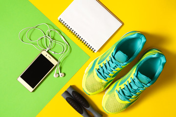 Sports equipment with shoes, skipping rope, blank notebook and mobile cellphone with earphones on colorful background. Top view, flat lay. Sport, fitness concept, healthy lifestyle