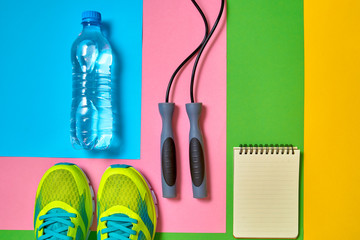Top view of sport shoes, skipping rope, empty blank notebook and bottle of water on colorful background, copy space. Flat lay. Sport, fitness concept, healthy lifestyle