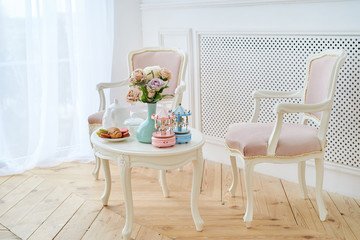 Two pink soft chairs and white wooden round table with breakfast, vase with flowers and merry-go-round musical carousel with horses. Beautiful modern interior, copy space